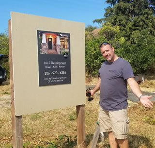 Matt Kuehn standing next to No 7 Development sign on customers lot for new home construction.
